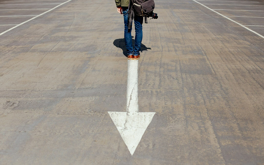 Person standing on arrow on road